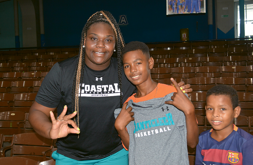 Alise Davis with two youth basketball clinic participants, one of whom proudly displays the new CCU T-shirt he received from Davis