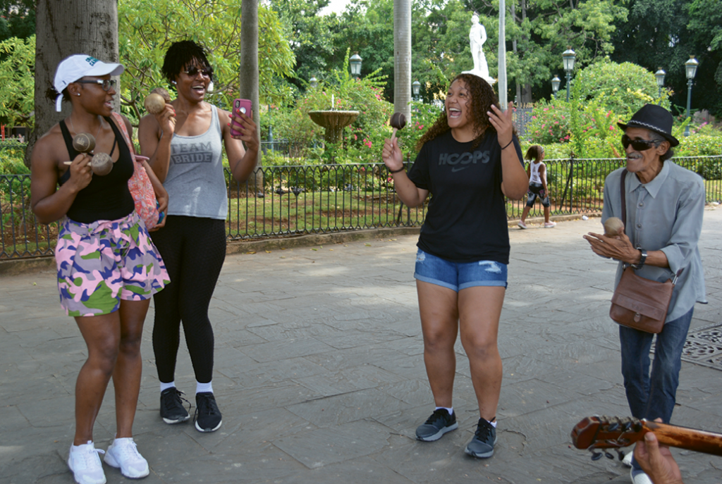 Twin sisters Janae and Janeen Camp and Aja Blount take a walking tour of Havana that includes an impromptu song and dance with local street performers.