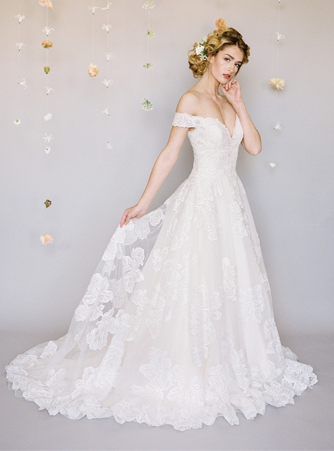 Madison James by Allure - This off-the-shoulder ball gown features applique from the bodice all the way down the train. Buttons run from the mid-back down and there is a subtle sparkle.  Fancy Frocks; $1,498