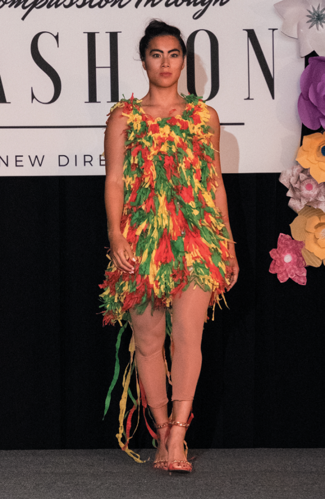 """Most Creative Description """"Streaming in Living Color"""" - Designer: Kim Clora - Model: Casselyn Aderholt - Materials: Zip ties and party streamers."""