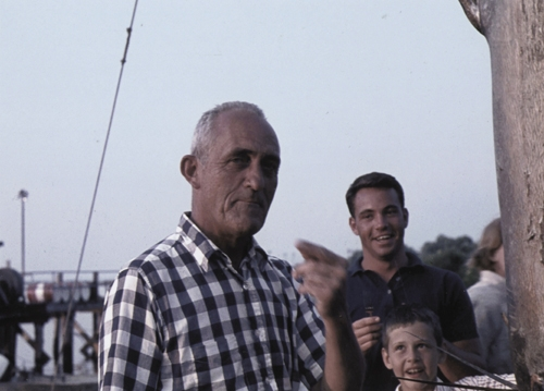 """Judge Ellison Smith III """"eating"""" the marlin as his son and Kenny Fitzgerald look on."""