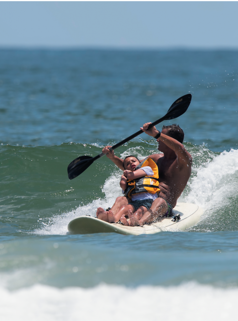 Vann Horne hits the waves with 8-year-old Shea Coleman.