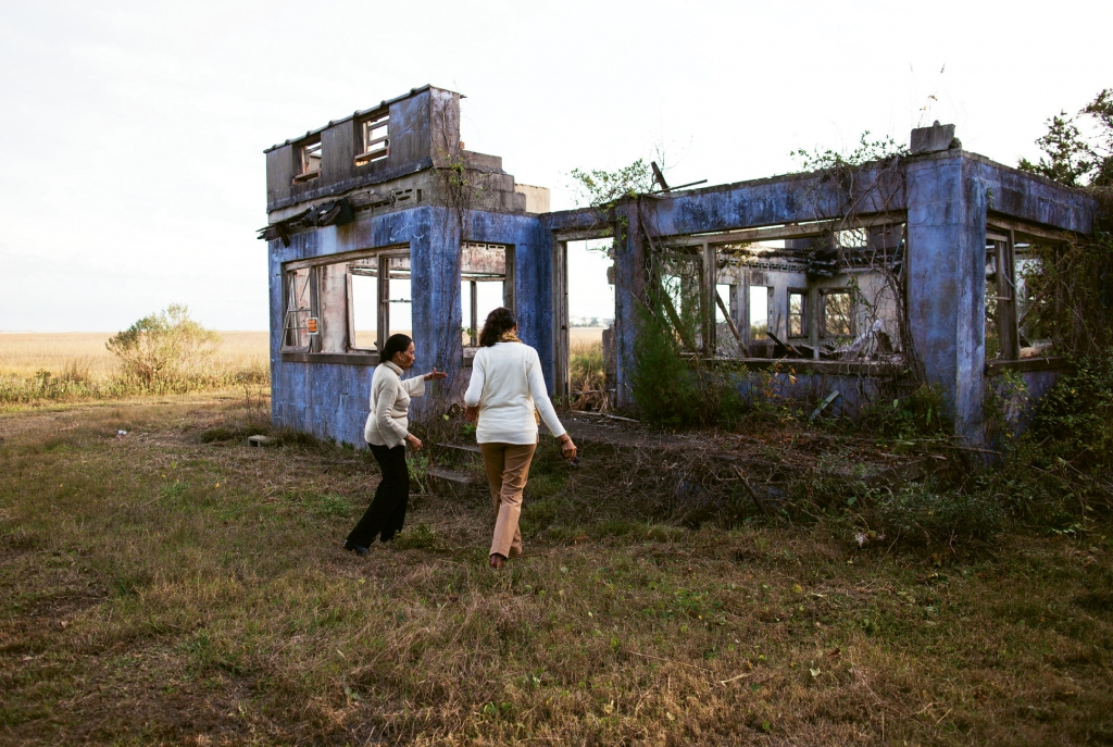 Gladys and Naomi walk the grounds of the aged, weather-battered Manigault family beach home, which is pictured above in its prime years.