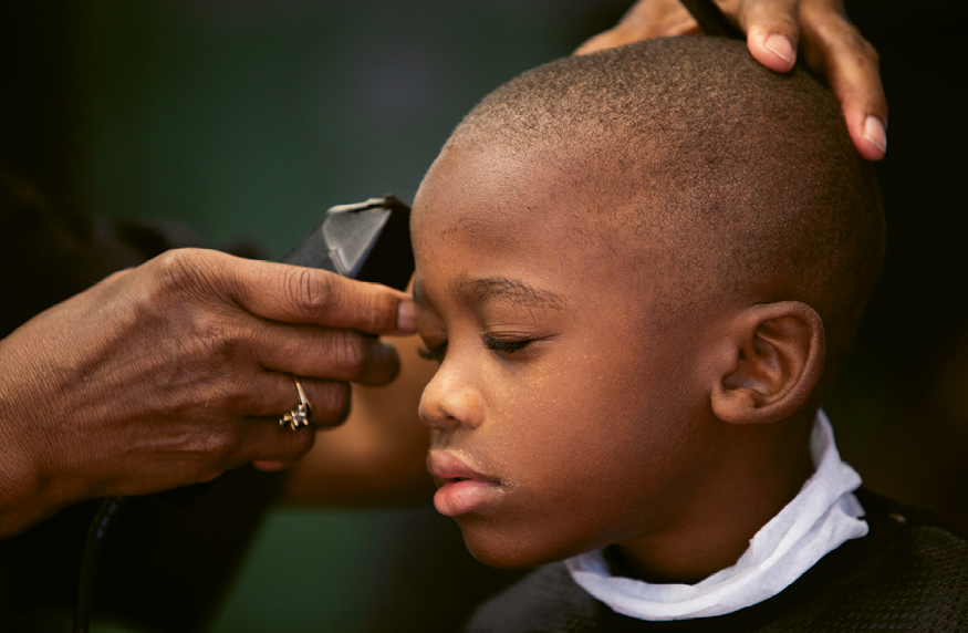 Aiden Hemmingway, 5, closes his eyes as Thomas puts the finishing touches on his haircut.