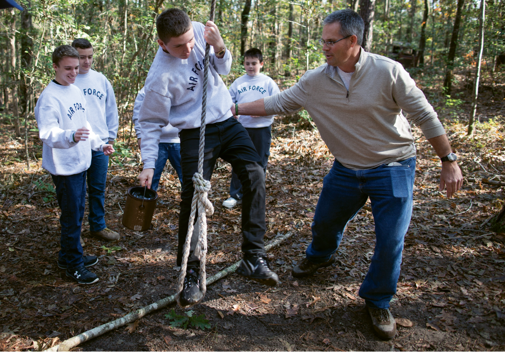 "Ben Abercrombie describes his job at Playcard Environmental Center as ""director, teacher, janitor."" Here he helps a student cross an imaginary pit as part of the low ropes, team-building ""Ropes Swing"" challenge."