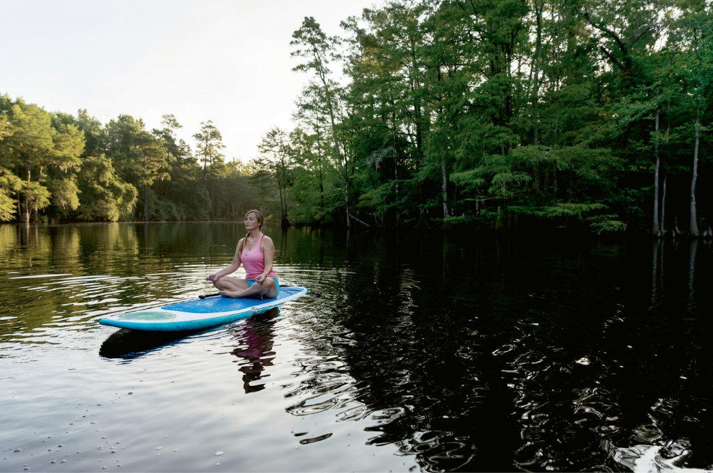 Calmly floating in the Kingston Lake section of the river, Cate Sutz uses her yoga board to balance and refuel.