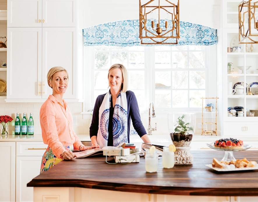 Homeowner Carmel Mamajek (left) and interior designer Robin Johnson of Urban Interiors consulted to bring about this striking kitchen renovation that incorporates old and new, texture and contrast. The mammoth center island is topped by rustic walnut, cabinets are inset with seeded glass and glitzy gold hardware and light fixtures get their sparkle on.