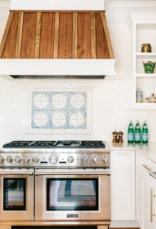 Classic Walker Zanger tile flanks both sides of a custom range hood in the kitchen and the newly designed mudroom features built-in cubbies and brick flooring in a herringbone pattern.